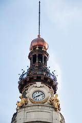 Reloj en torre de edificio con esculturas doradas.