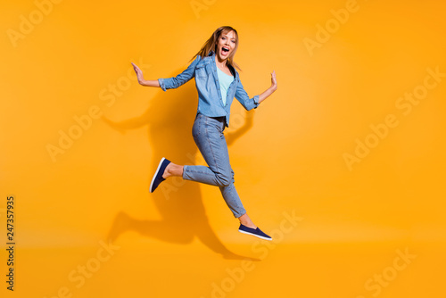 Leinwandbild Motiv Full length body size photo yelling  jumping high beautiful she her lady little low prices announce black friday shopping store wearing casual jeans denim shirt clothes isolated on yellow background