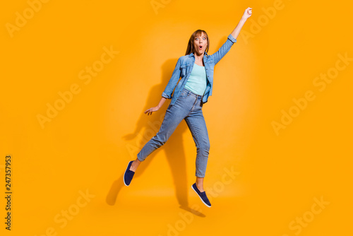 Leinwanddruck Bild Full length body size photo yelling  in flight jumping high beautiful she lady not believe umbrella take her in sky wearing casual jeans denim shirt clothes isolated on yellow background