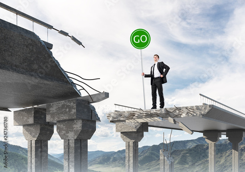 Young businessman holding street safety sign. - 247361780
