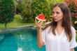 Portrait thoughtful girl with long hair holding slice of watermelon in her hand