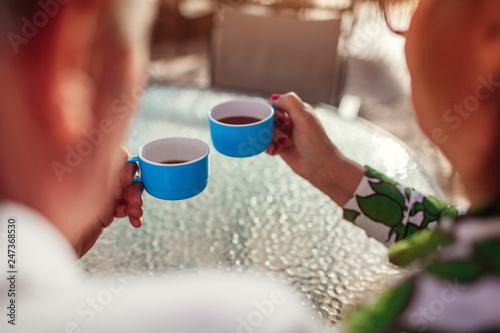 Leinwandbild Motiv Senior couple drinking tea in hotel cafe. People enjoying vacation. Close-up