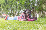 Afroamerican girl laying down on the grass making school lesson - 247373516