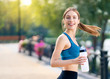 Leinwanddruck Bild - Happy woman with bottle of water, during morning jogging