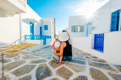 Mum and daughter in white hats sit hugging and taking great selfie on the beatiful sunshine greek street