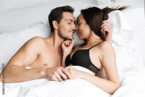 Leinwanddruck Bild Young loving couple indoors in home in bed lies hugging and kissing.