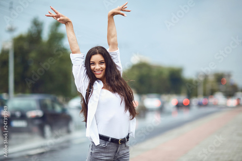 Leinwandbild Motiv Happy brunette girl holding her hands up on a city street