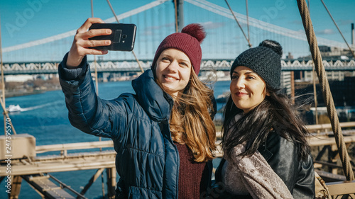 Foto Murales Two friends in New York walk over the famous Brooklyn Bridge