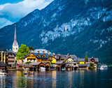 evening scenery of beautiful Hallstatt at the wide lake on the background of rocky forested mountains