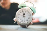 Man is holding an alarm clock in the hand, blurry background - 247399560