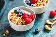 Leinwandbild Motiv Vegetarian breakfast, a bowl with organic granola, fresh raspberries and blueberries and coconut yoghurt.