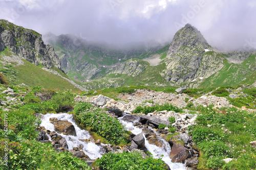 stream flowing in rocky mountain under cloudy sky