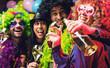 Leinwanddruck Bild - Lachende Freunde in bunten Kostümen trinken Sekt bei einer Karneval party .