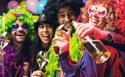 Leinwanddruck Bild Lachende Freunde in bunten Kostümen trinken Sekt bei einer Karneval party .