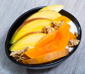 Sweet pumpkin and mango and whipped cream with  oat-flakes  at plate