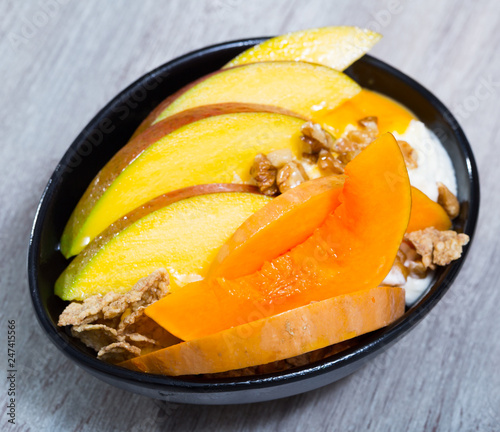 Sweet pumpkin and mango and whipped cream with  oat-flakes  at plate - 247415566