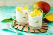Leinwanddruck Bild - Homemade breakfast. Healthy food concept. Greek yogurt with mango on a wooden board on stone or concrete table.