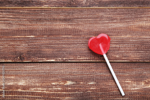 Heart shaped lollipop on brown wooden table | Buy Photos | AP Images