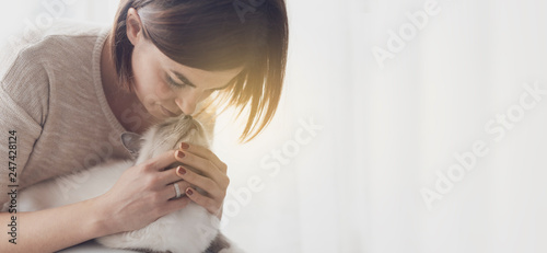 Woman hugging and petting her cat