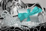Little gift box with cyan blue ribbon and black and white lacy lingerie background - 247436558