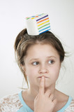 a pensive girl with a sguishy toy cake on her head and her index finger near the lips - 247437385