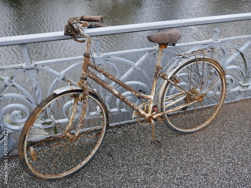 Rusted old lady's bicycle. It was parked long ago on a bridge railing and then forgotten.