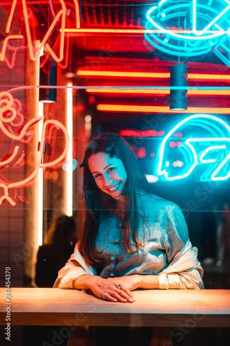 fototapeta na ścianę Beautiful girl in a window cafe and looks at the camera