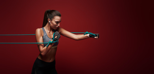 Use it or lose it. Sportswoman performs exercises with resistance band over red background © dima_sidelnikov