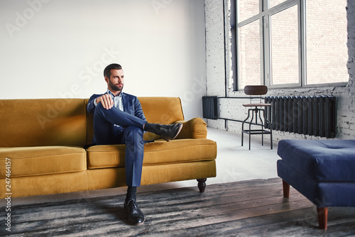 Leinwanddruck Bild Feeling relaxed...Handsome and stylish young businessman is resting on sofa and thinking about business ideas