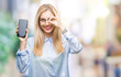 Leinwanddruck Bild - Young beautiful blonde business woman showing screen of smartphone over isolated background with happy face smiling doing ok sign with hand on eye looking through fingers
