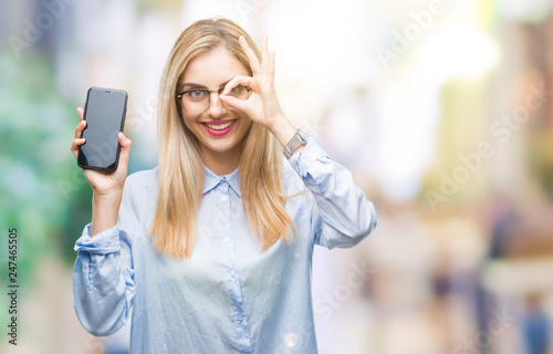 Leinwanddruck Bild Young beautiful blonde business woman showing screen of smartphone over isolated background with happy face smiling doing ok sign with hand on eye looking through fingers