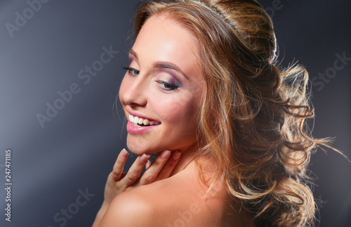 Beautiful woman with curly long hair on dark background .