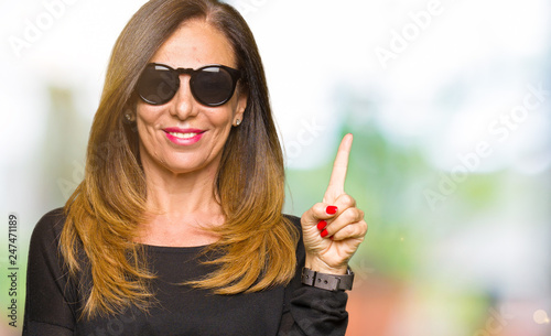 Leinwandbild Motiv Beautiful middle age woman wearing sunglasses with a big smile on face, pointing with hand and finger to the side looking at the camera.