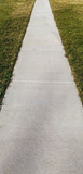 Perspective of neighborhood sidewalk flanked by grass. - 247476938