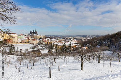 Snowy Prague City with gothic Castle from Hill Petrin in the sunny Day, Czech republic - 247477101