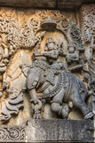 Halebidu, Karnataka, India - November 2, 2013: Hoysaleswara Temple of Shiva. Closeup of statue on side of main sanctuary, where Lord Shiva and Devi Parvati sit on elephant. Gray stone with brown back.