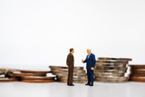 Miniature people, couple businessman standing on pile coins background using as business corporation and financial concept - 247486149