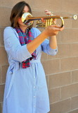 Female jazz trumpet player blowing her horn outside.