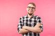 Portrait of happy fashionable handsome man in plaid shirt and glasses crossing hands on pink background