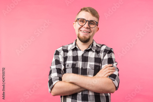 Leinwandbild Motiv Portrait of happy fashionable handsome man in plaid shirt and glasses crossing hands on pink background