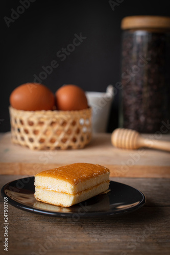 layer vanilla flavoured cake place on black plate on the wooden table there are coffee bean in glass bottles and bucket of water ceramic and basket of eggs place backside.