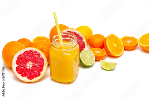 Freshly blended yellow and orange fruit smoothie in glass jar. Glass jar mugs with orange health smoothie, lime, grapefruit, lemon, tangerine. Selective focus. Copy space. Vegetarian food concept.   © Elena Verba