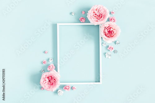 Leinwanddruck Bild Flowers composition. Photo frame, rose flowers on pastel blue background. Valentines day, mothers day, womens day, spring concept. Flat lay, top view, copy space