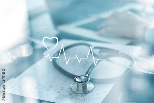 Stethoscope with heart beat report and doctor analyzing checkup on laptop in health medical laboratory background. © ipopba