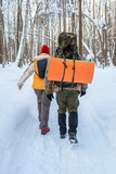 Tourists with racksacks going along winter path in the forest, rear view