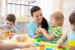 Leinwanddruck Bild - Tutor teaches children handcraft in kindergarten or playschool