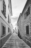 Black and white picture of a narrow street in Alcudia old town, Mallorca, Spain.