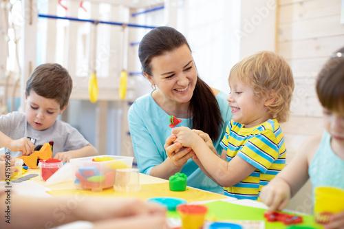 Leinwandbild Motiv Tutor teaches children handcraft in kindergarten or playschool