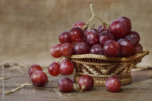 Foto Murales a bunch of red grapes on bamboo basket