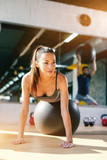 Close up of beautiful Caucasian woman with ponytail and long brown hair doing exercises with pilates ball in gym. In background reflection of man with pilates ball.